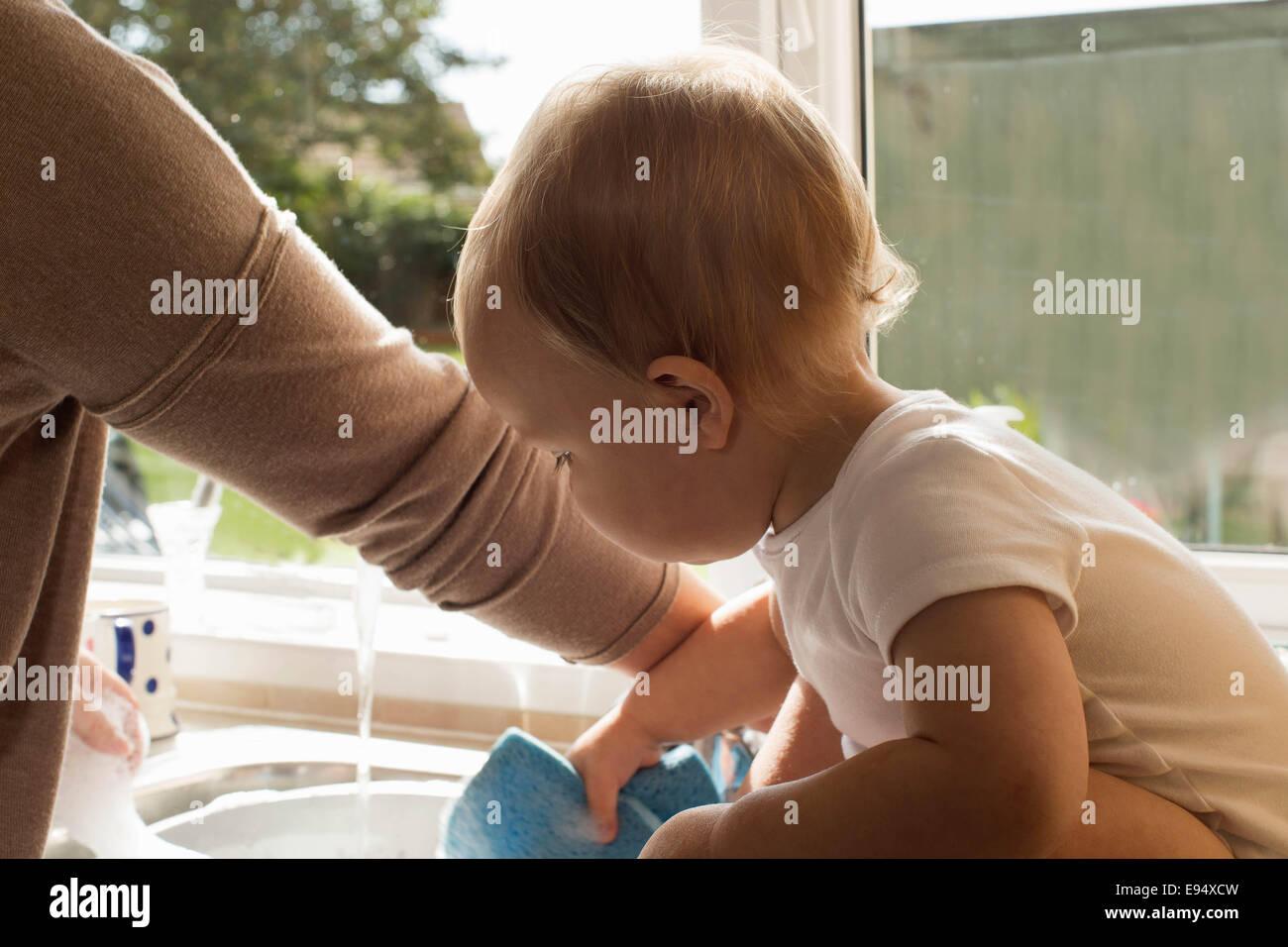 Bebé jugando con el agua en la cocina. Foto de stock