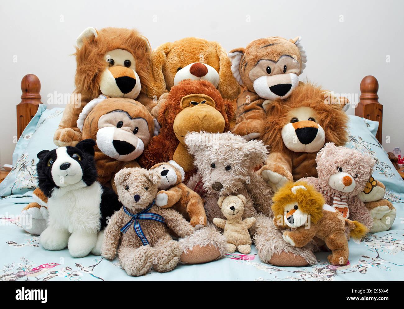 Una colección de juguetes de peluche suave en una cama Foto de stock