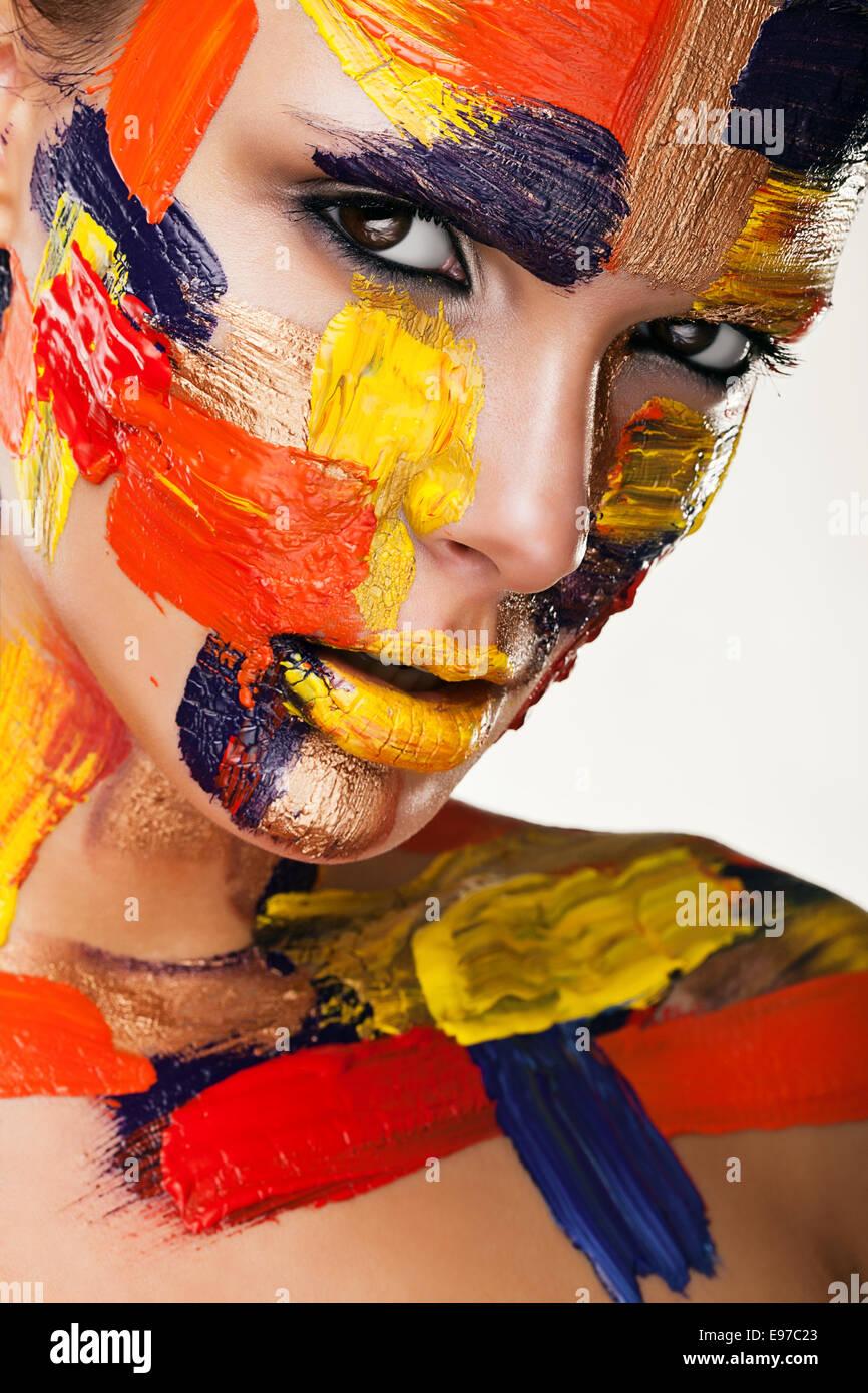 Morena atractiva en coloridas pinturas Imagen De Stock