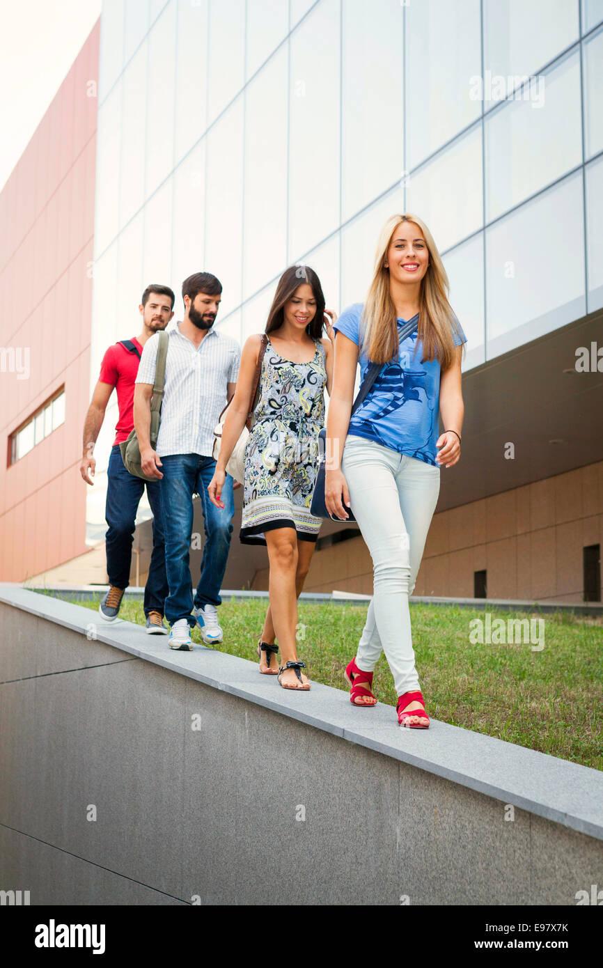 Un grupo de estudiantes universitarios a caminar en una fila Imagen De Stock