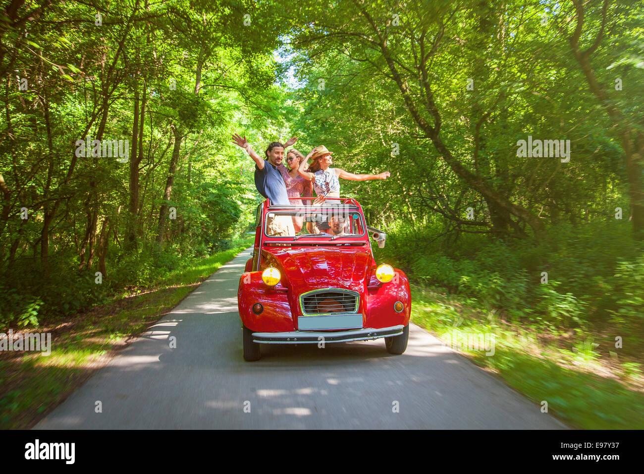 Los jóvenes en rojo vintage car divirtiéndose Imagen De Stock