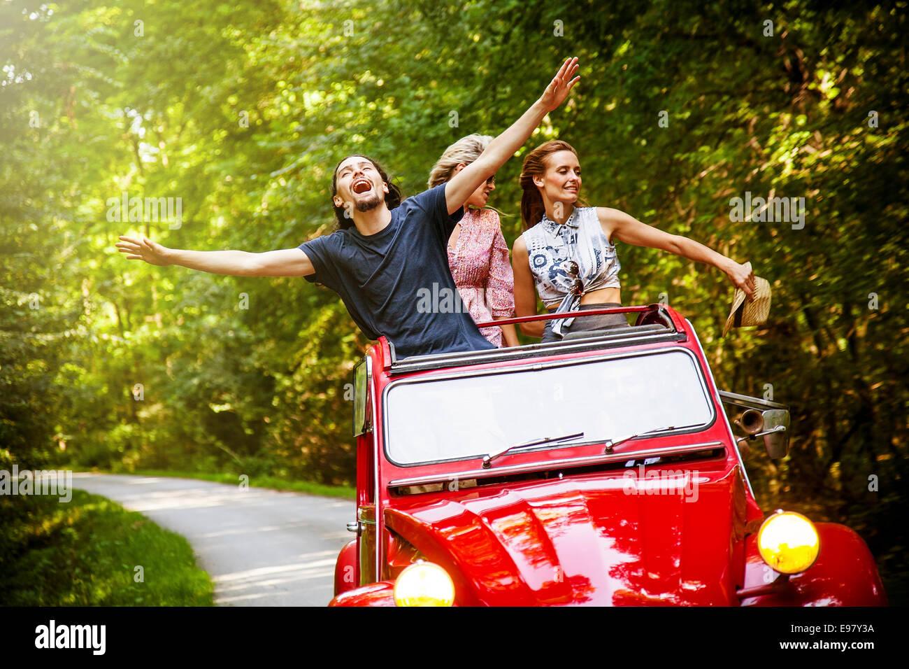 Los jóvenes en rojo vintage car jugando Imagen De Stock