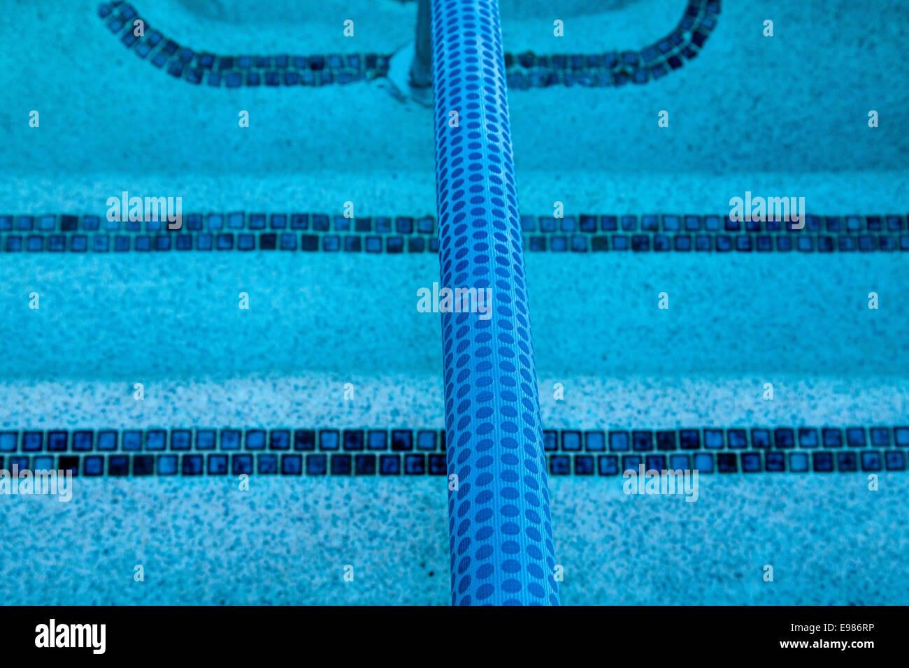 En el agua. Los escalones y pasamanos en las tranquilas aguas de la piscina de agua azul. Imagen De Stock