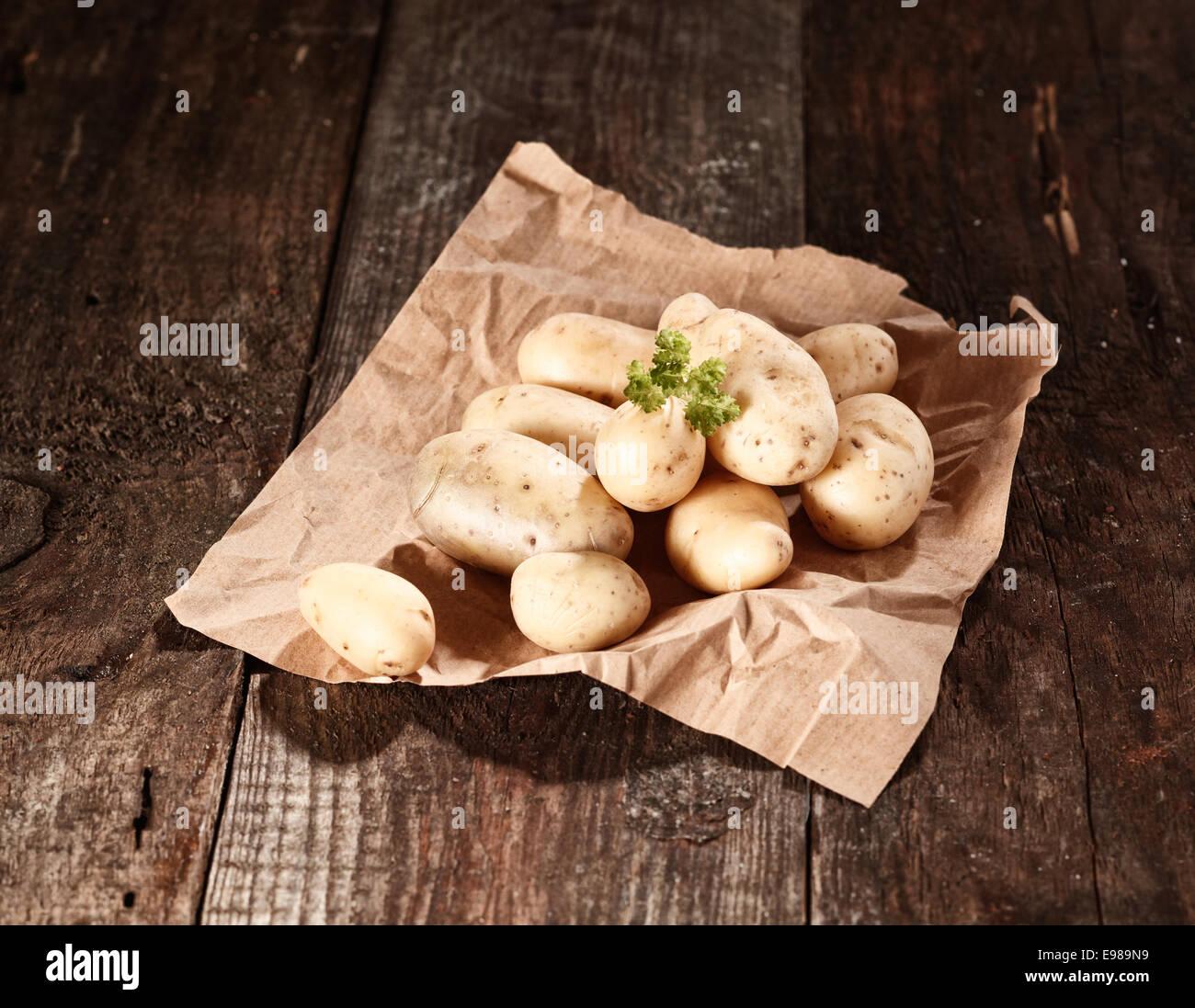 Granja de patatas lavadas fresco aparece en el doblado de papel marrón sobre una mesa de madera Imagen De Stock