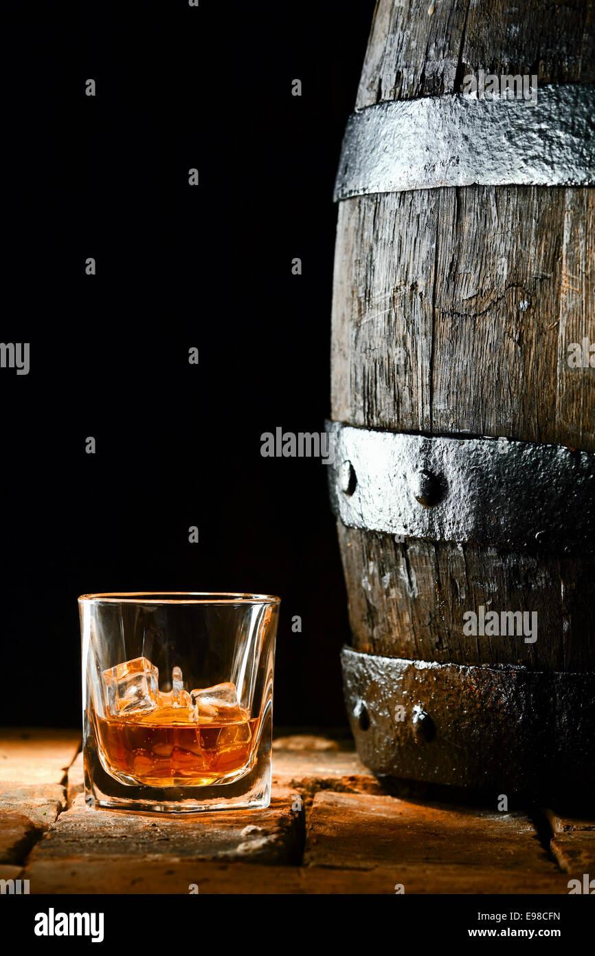 Copa de Oro premium madurado brandy o whisky en las rocas junto a un viejo barril de roble de pie sobre ladrillos Imagen De Stock