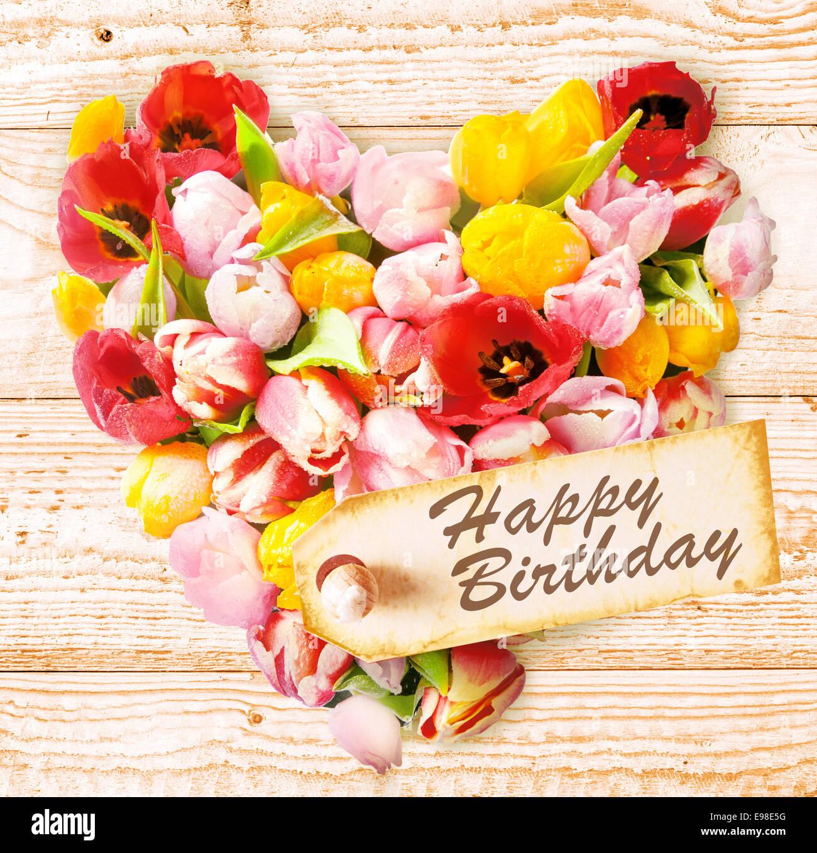 Corazón floral sentimental de felicitación de cumpleaños con un arreglo en forma de corazón simbólico de tulipanes, sobre un fondo de madera rústica con el mensaje - Feliz cumpleaños - en una etiqueta del regalo para un ser querido Foto de stock