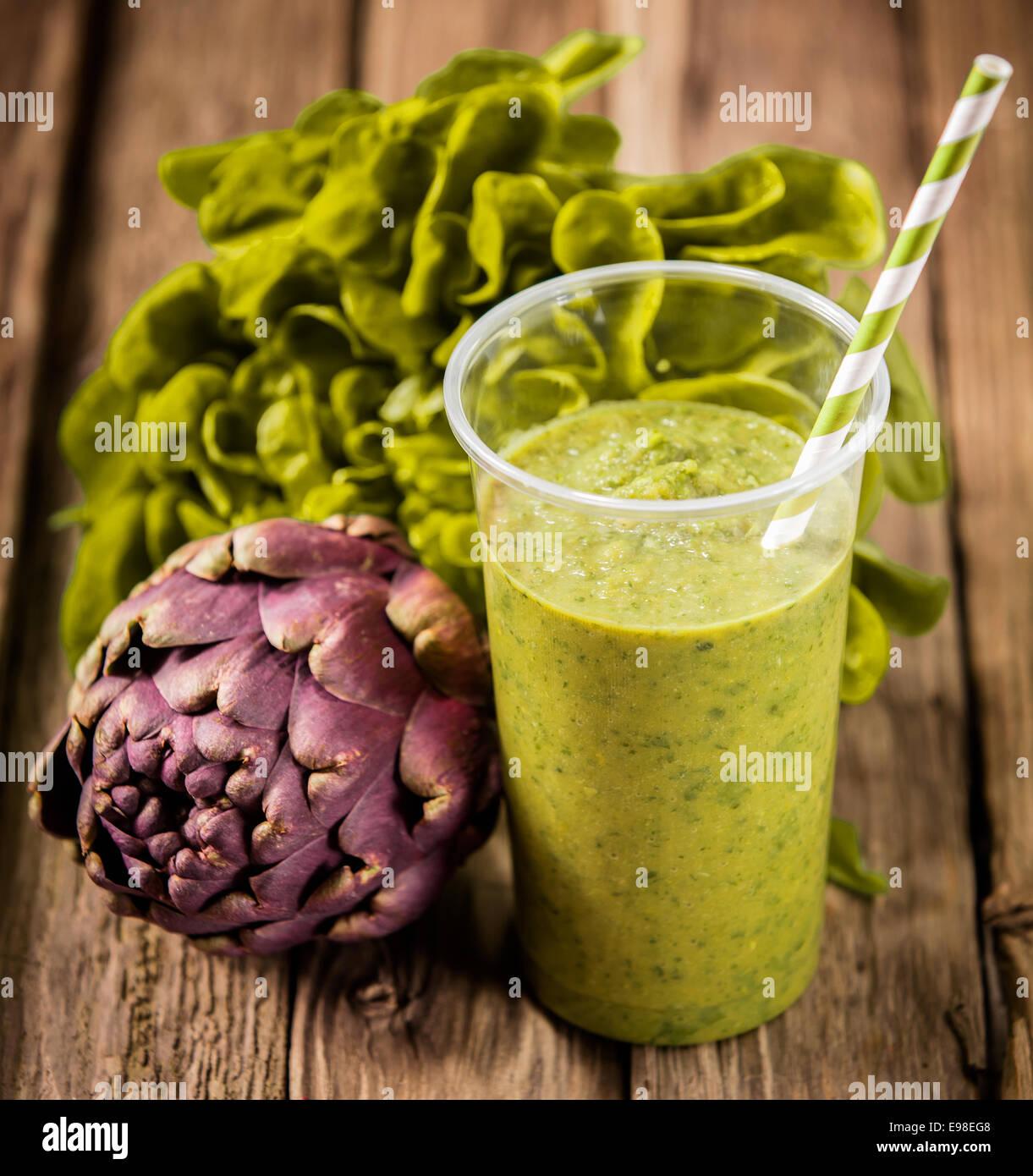 Batido de vegetales saludables con lechuga y alcachofa mezcladas con yogur servido con un patrón de espiral alto Foto de stock
