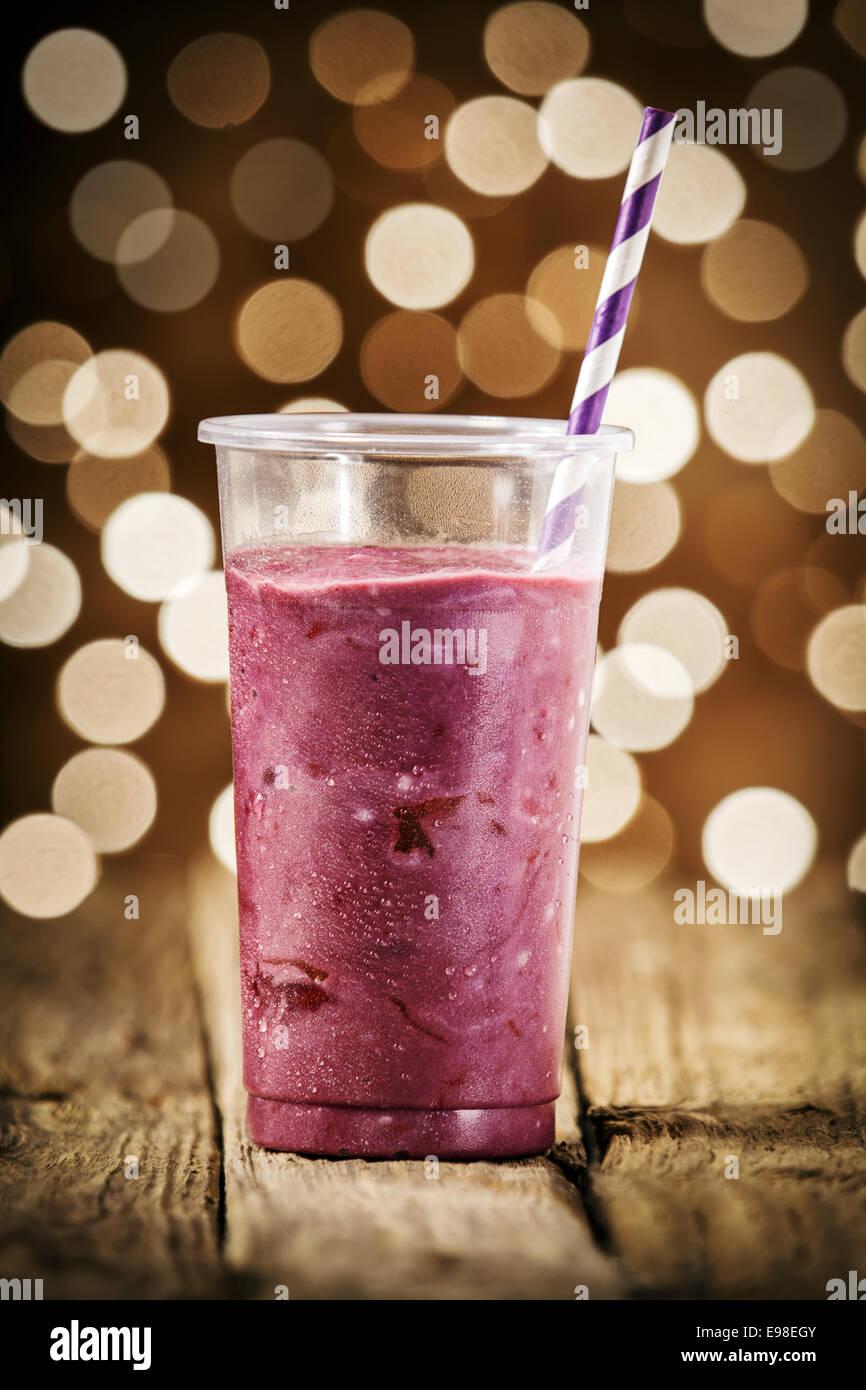 Festiva smoothie de arándanos mezclado con yogur y helado para un verano refrescante bebida contra un bokeh Imagen De Stock