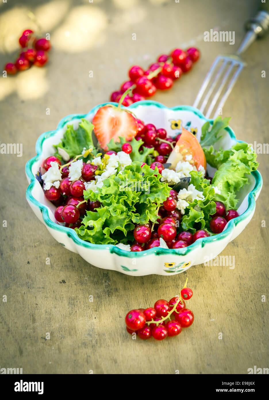 Deliciosa ensalada de verano fresco en un tazón sobre fondo de madera. Bueno para los vegetarianos. Imagen De Stock
