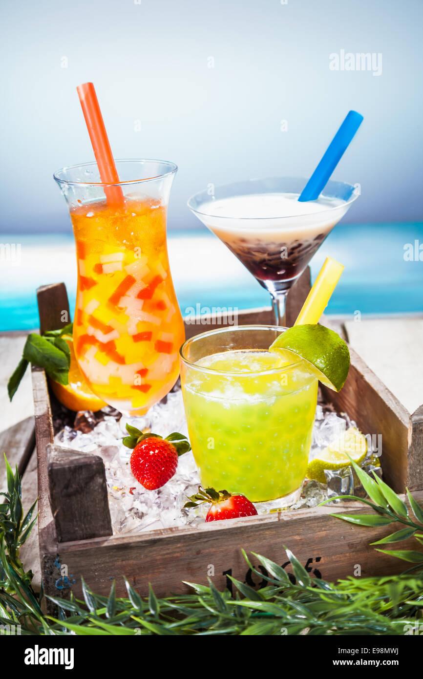 Trío de coloridos cócteles tropicales mezclado con frutas en formas diferentes vasos servidos con vistas a una playa Foto de stock