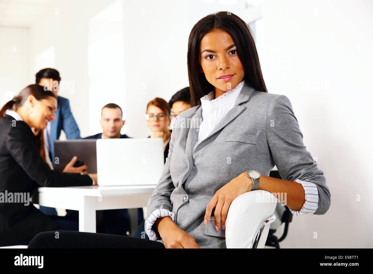 La empresaria sentado en la silla de oficina en frente de reunión de negocios Imagen De Stock