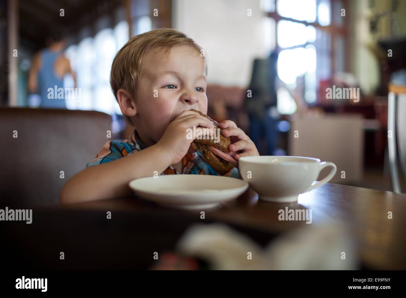 Niñito habiendo sándwich en un café Imagen De Stock