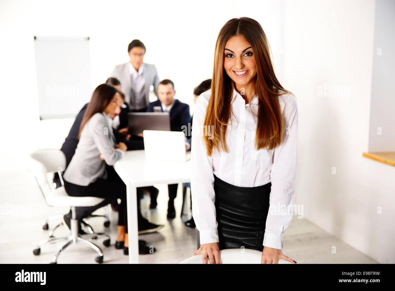 Retrato de un feliz empresaria en frente de reunión de negocios Imagen De Stock