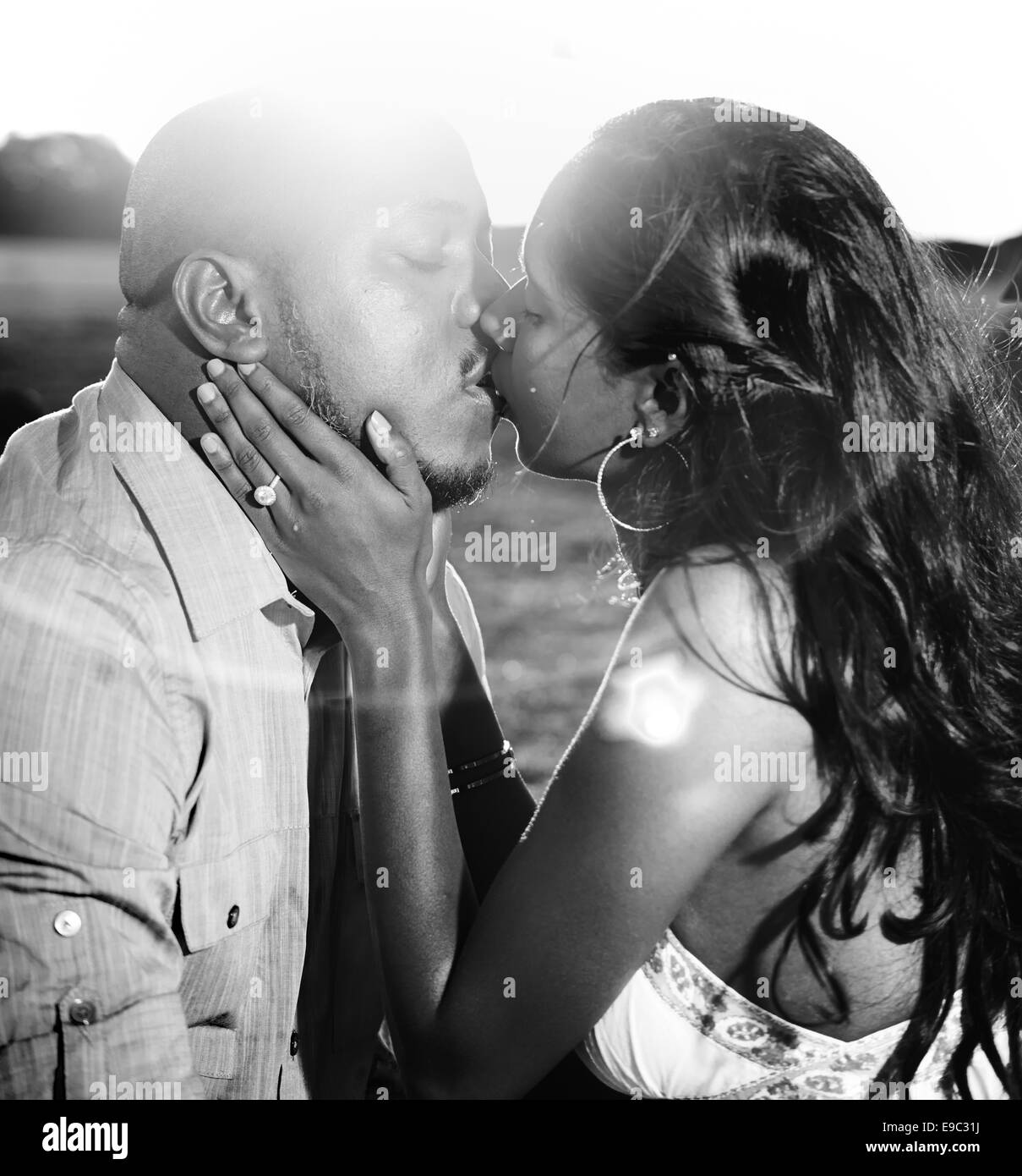 Pareja besándose con el brillo del sol en blanco y negro Imagen De Stock
