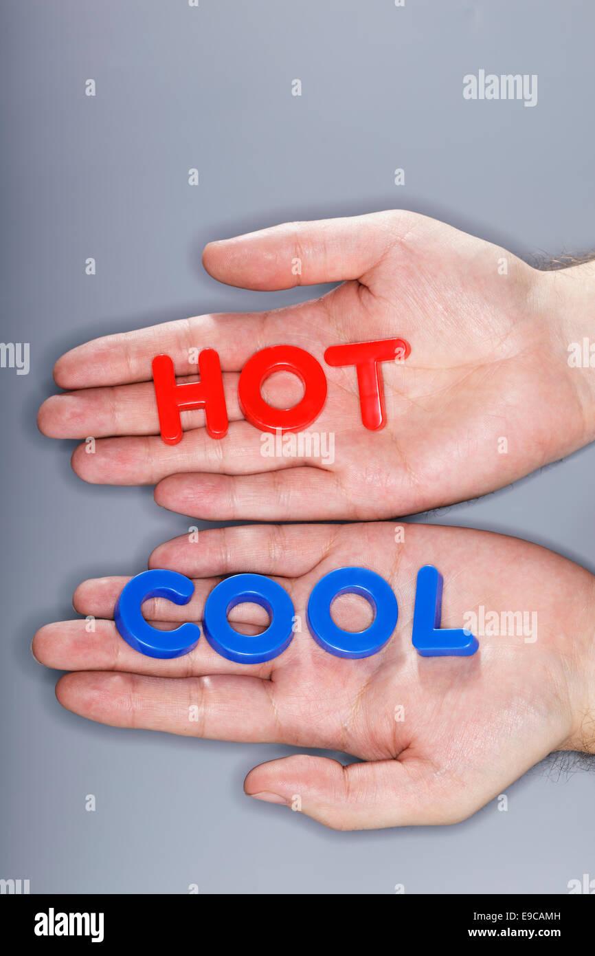 Hombre con letras de plástico caliente y frío en sus manos. Imagen De Stock