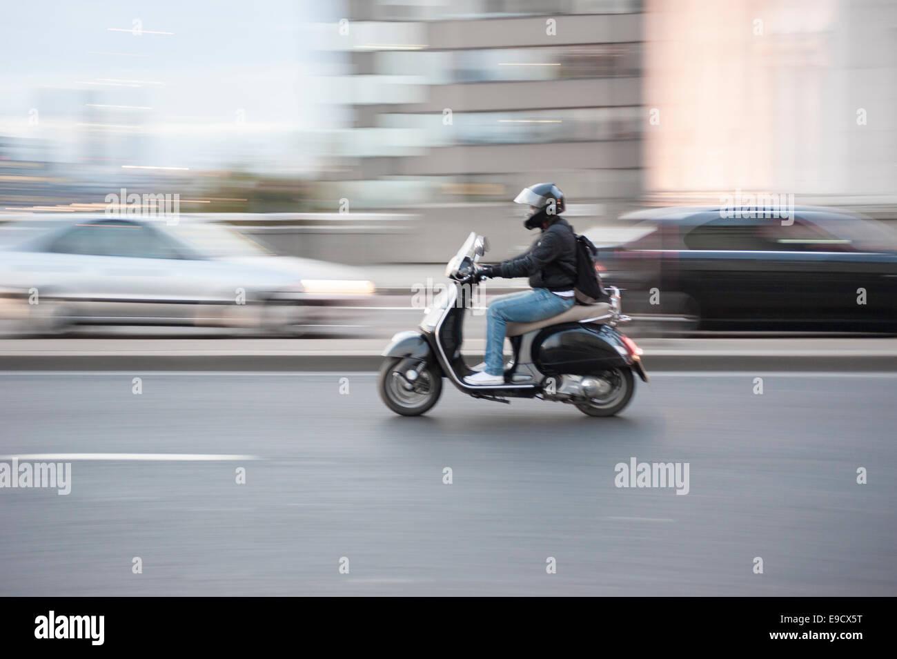 Hombre en un scooter con el desenfoque de movimiento, Londres, Reino Unido. Imagen De Stock