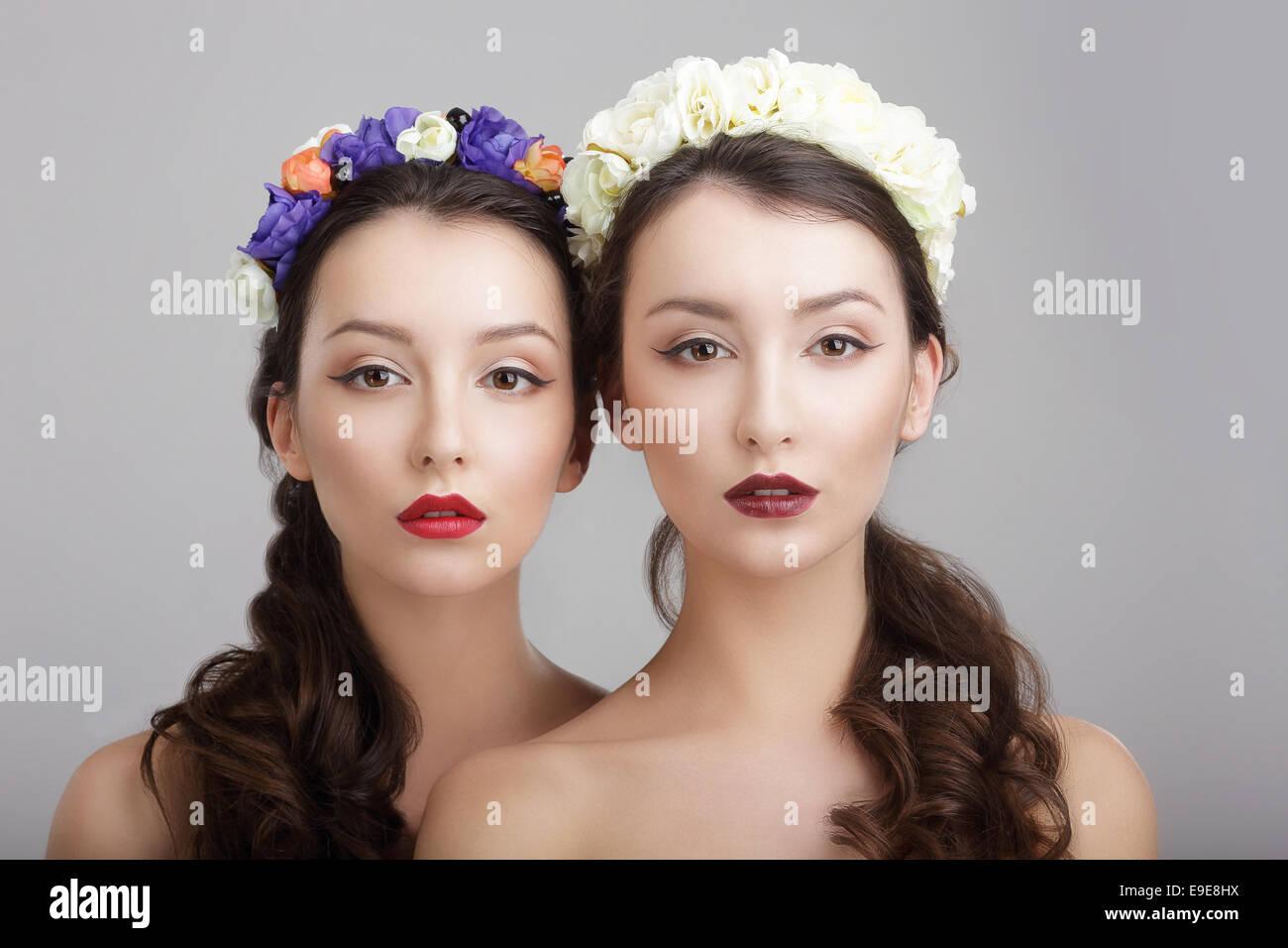 La elegancia. Dos mujeres con coronas de flores. Fantasy Imagen De Stock