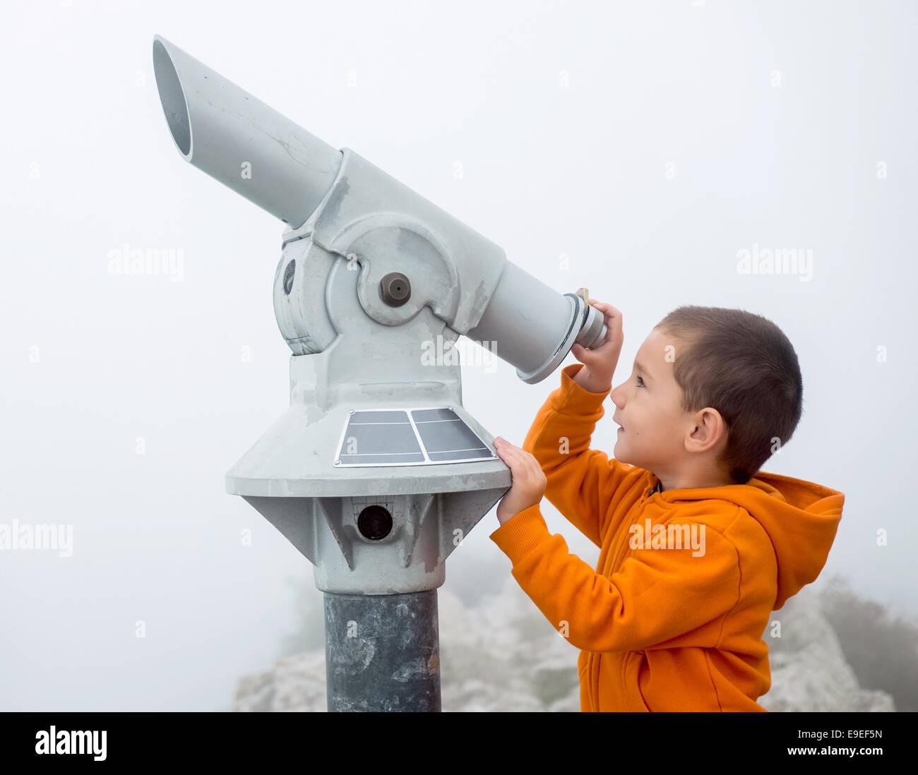 Niño mirando hacia el cielo a través de un catalejo Foto de stock