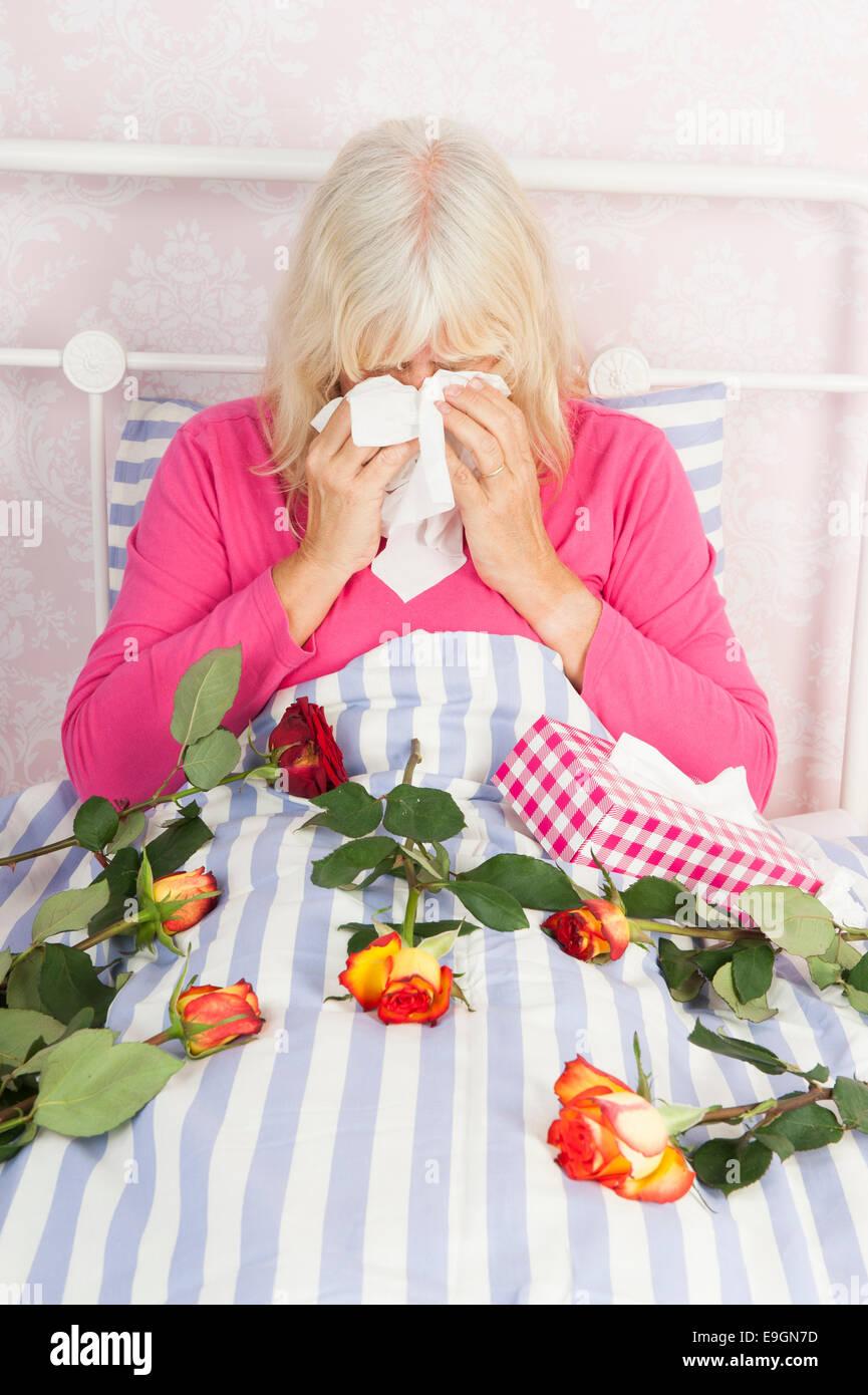 Triste mujer en pijama rosa sentada en la cama con un ramo de rosas y tejidos Imagen De Stock