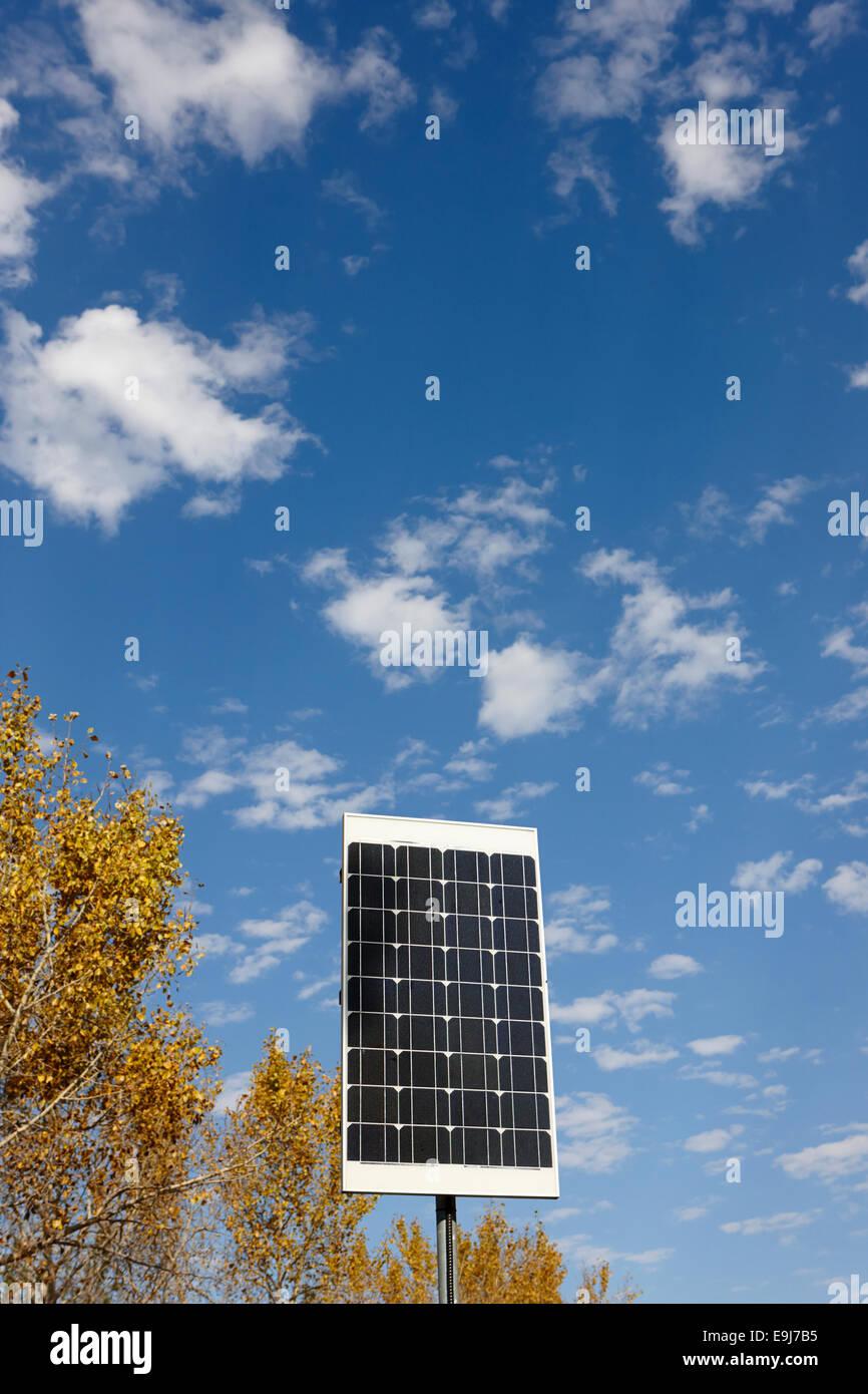 Panel solar de tamaño mediano contra el azul cielo nublado en día soleado Imagen De Stock