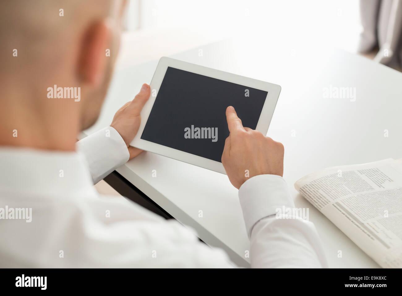 Adulto medio empresario utilizando equipo digital a la mesa en la oficina en casa Imagen De Stock