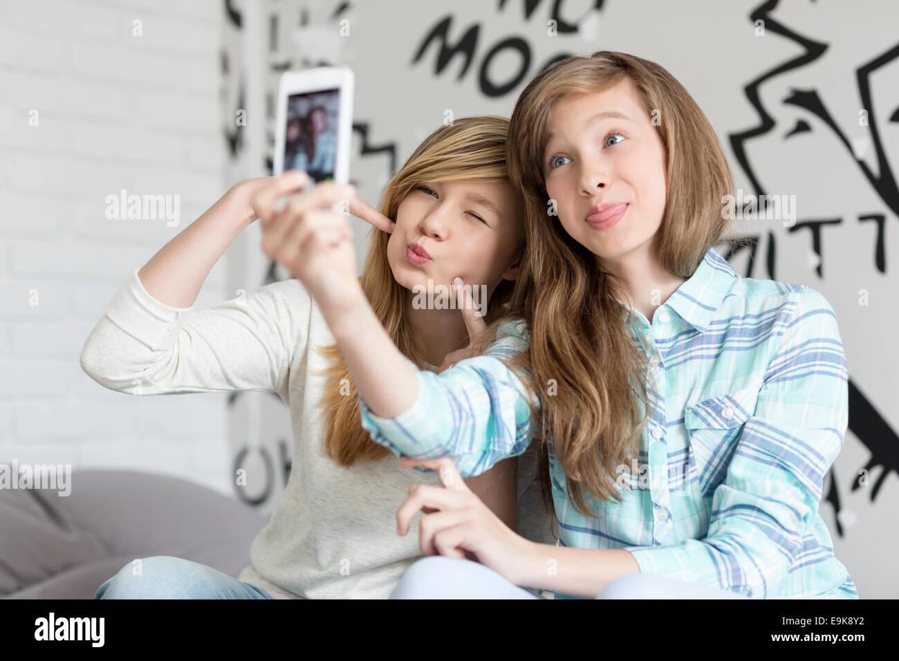 Cute hermanas faneca mientras toma fotos con el teléfono inteligente en casa Imagen De Stock
