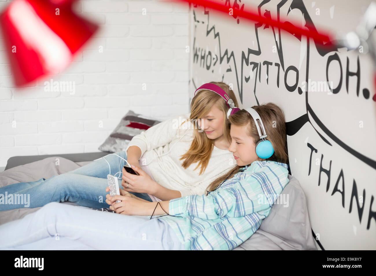 Hermanas relajado escuchando música en casa Foto de stock