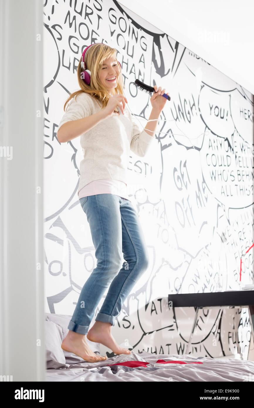 Emocionada chica escuchando música mientras canta con cepillo en casa Foto de stock