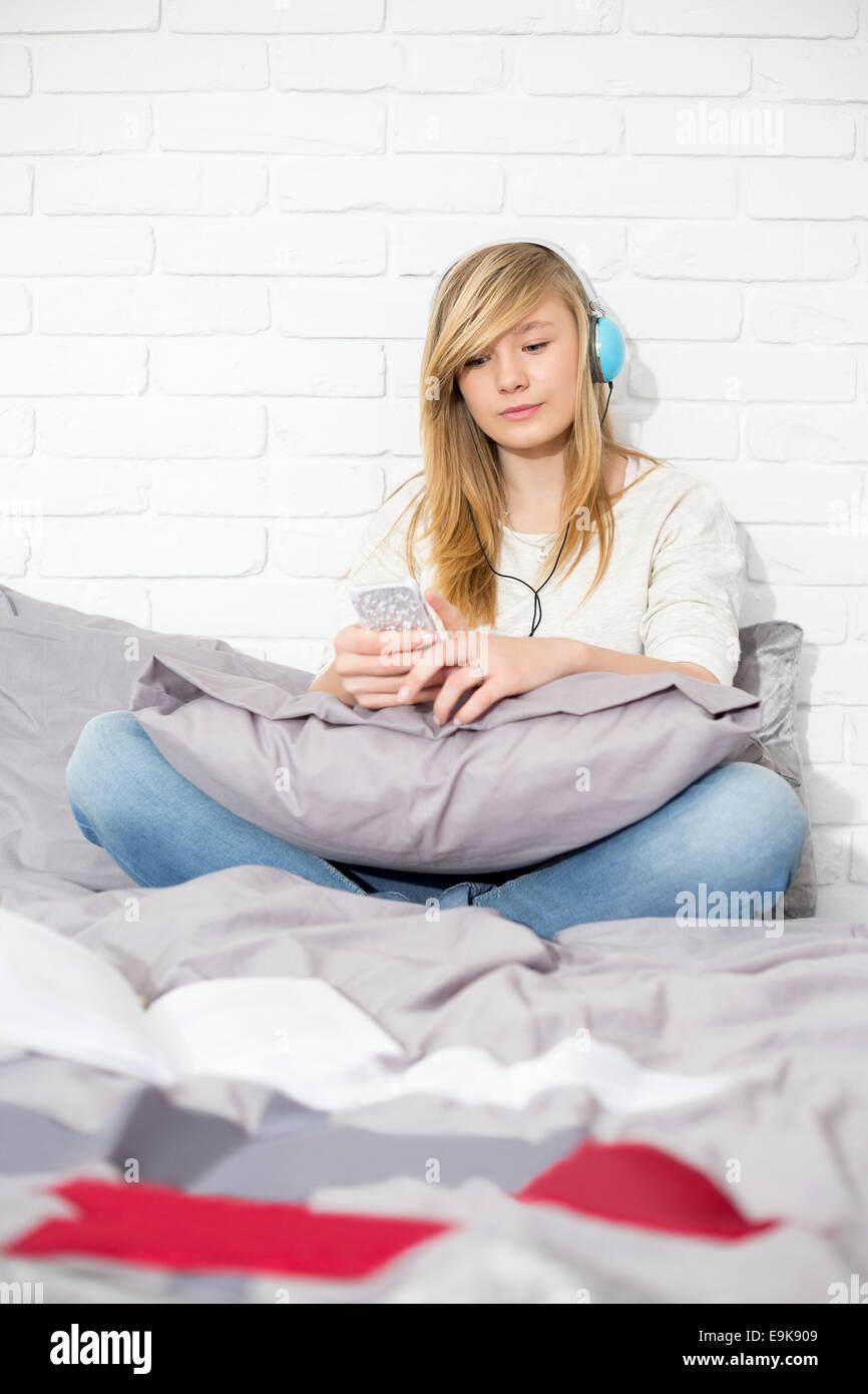 Longitud completa de adolescente escuchando música en el dormitorio Foto de stock