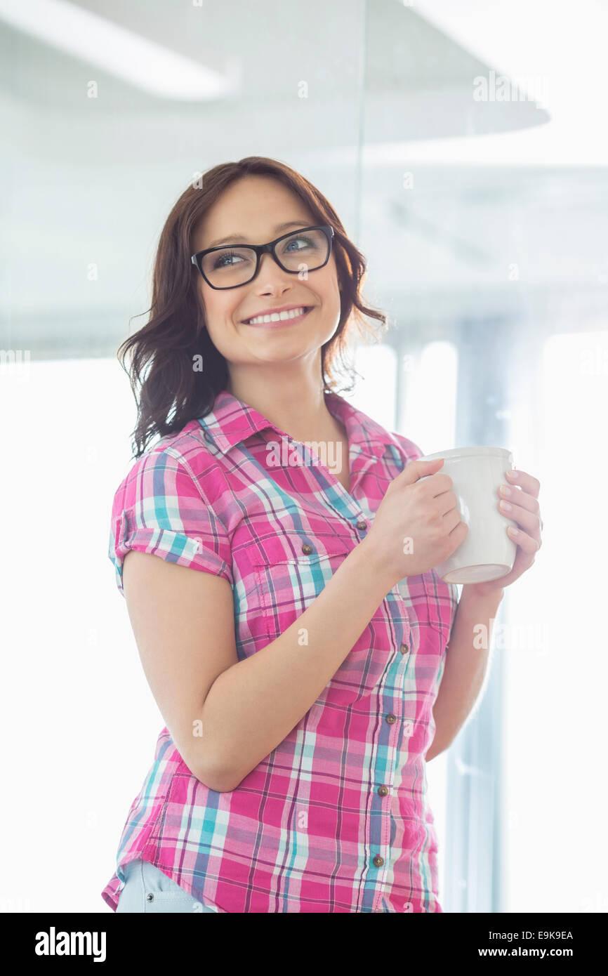 Feliz empresaria mirando a otro lado mientras mantiene taza de café en la oficina creativa Imagen De Stock