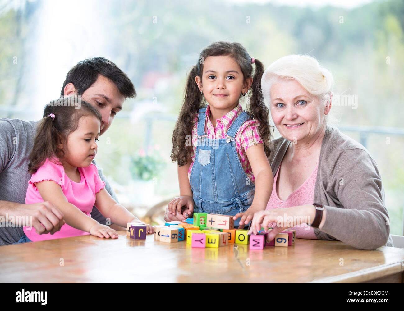 Tres generaciones de la familia feliz jugando con bloques de letras en casa Imagen De Stock