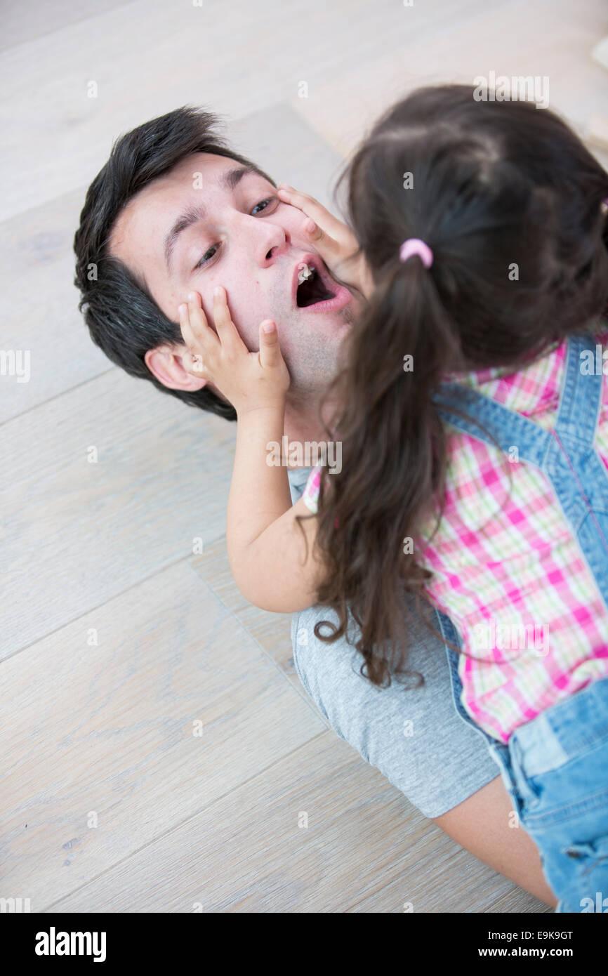 Juguetón hija encima del padre en el hogar Imagen De Stock