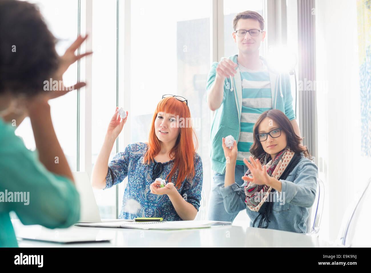 Empresarios enojado lanzando bolas de papel de compañero de oficina creativa Foto de stock