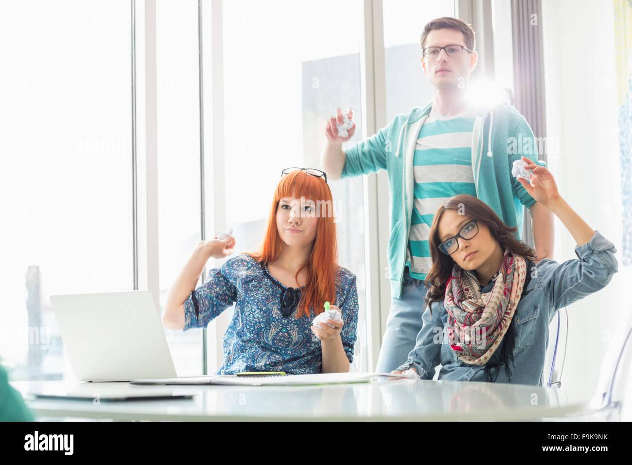 Empresarios enojado lanzando bolas de papel en la oficina creativa Imagen De Stock
