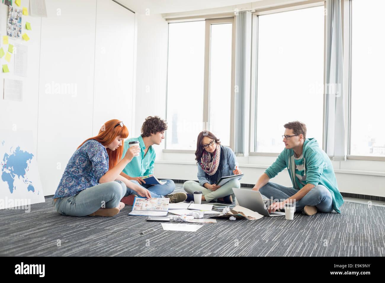 Los empresarios que trabajan en el suelo en el espacio de trabajo creativo Imagen De Stock