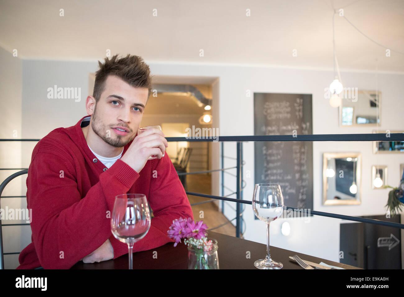 Retrato de seguros joven agua potable de vidrio en cafe Imagen De Stock