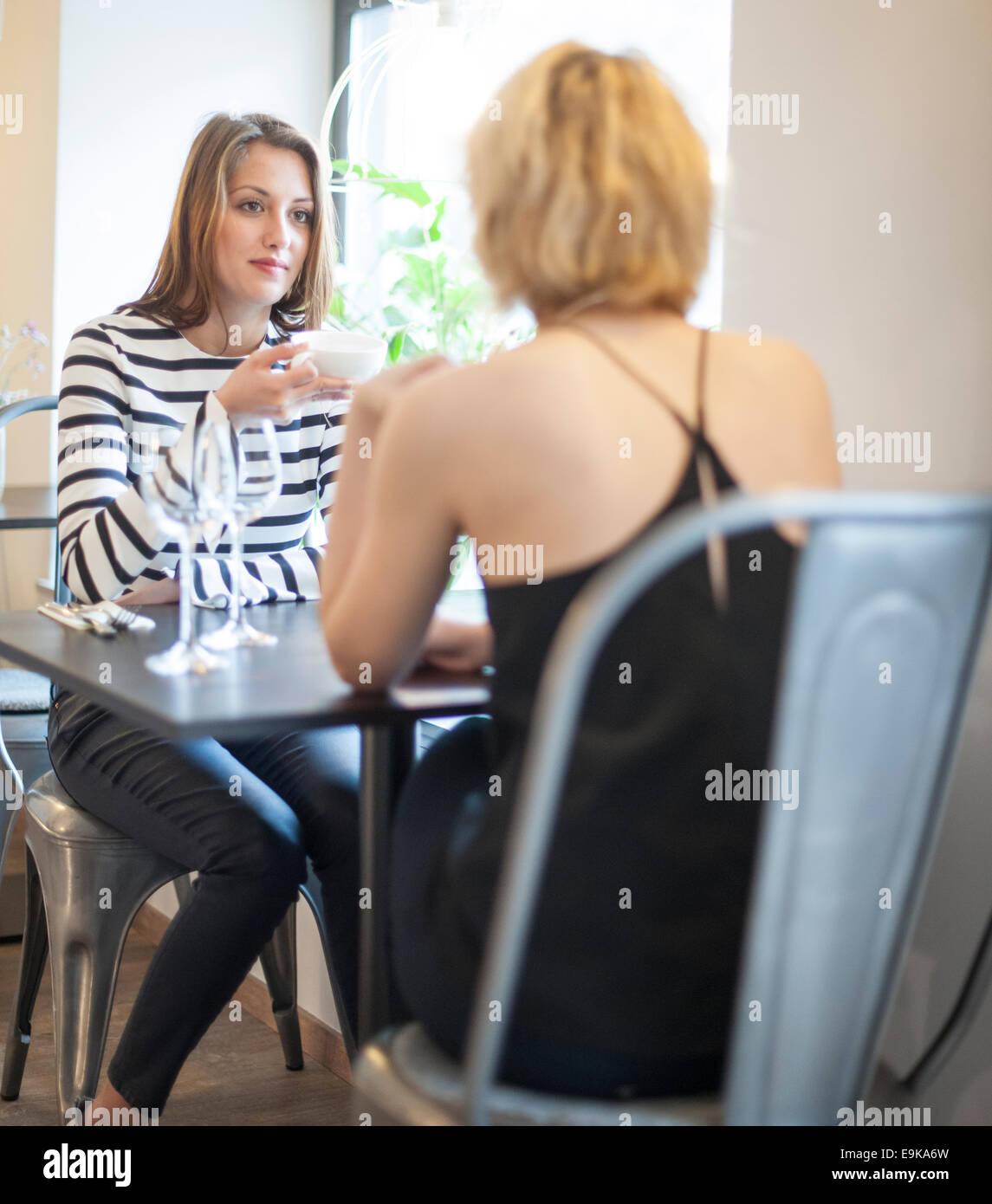Las hembras jóvenes amigos que el café en Imagen De Stock