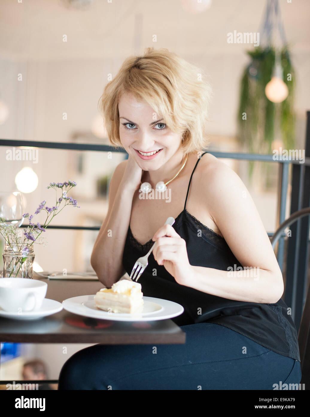 Retrato de mujer joven feliz comiendo pastel de café Foto de stock