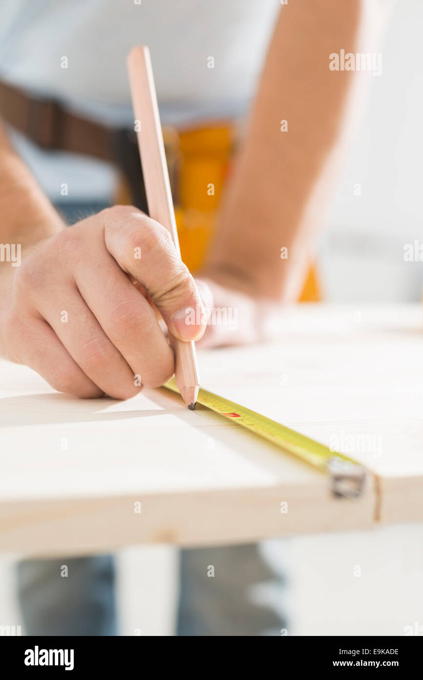 Central de carpintero marcando el cuadro con cinta de medir Imagen De Stock