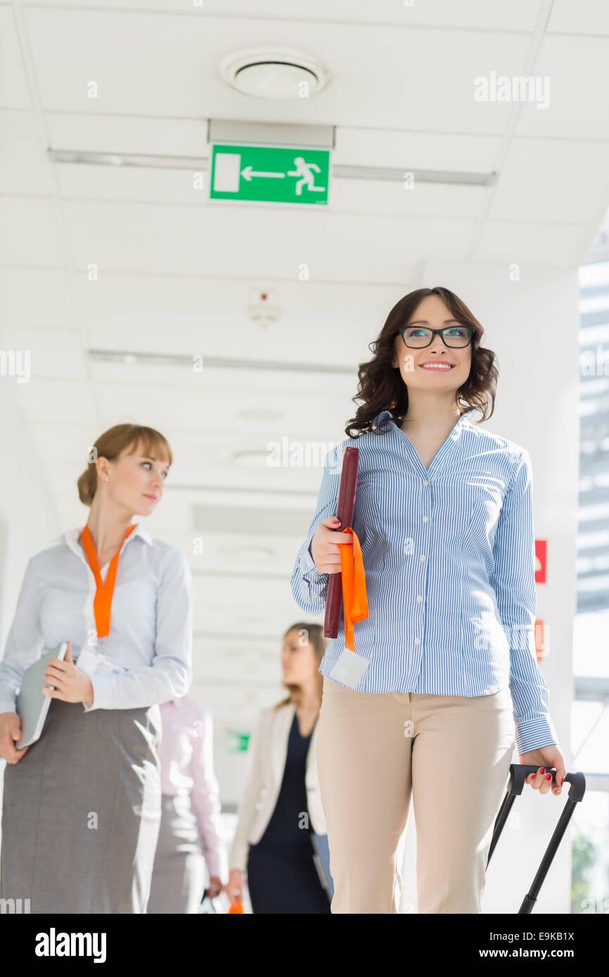 Feliz empresaria arrastrar equipaje mientras camina con el equipo en el aeropuerto Imagen De Stock