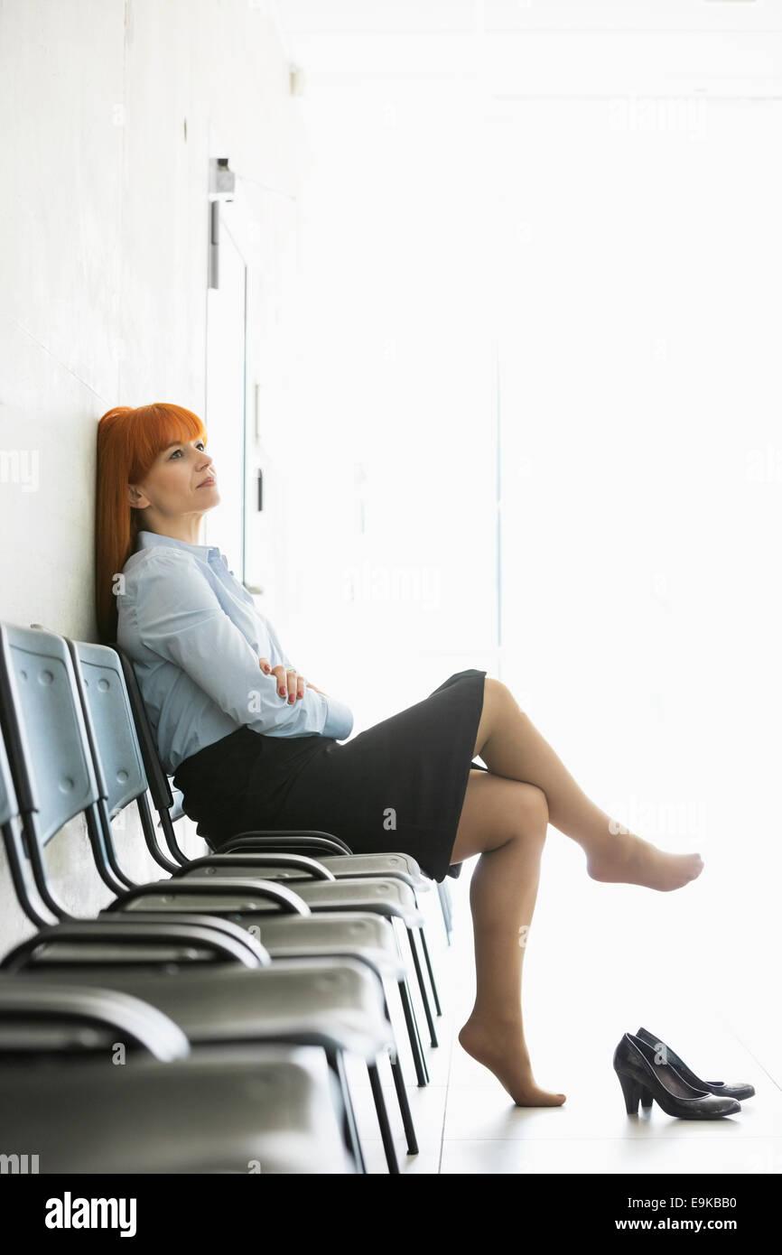 Pensativo empresaria sentarse con las piernas cruzadas en una silla de oficina Imagen De Stock