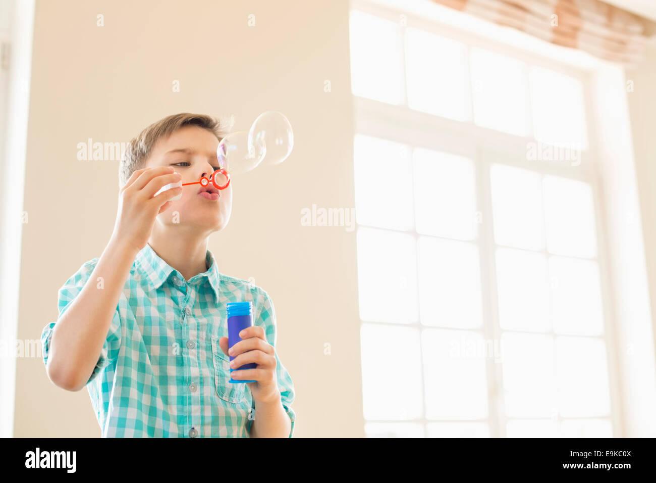 Muchacho soplando burbujas en casa Imagen De Stock