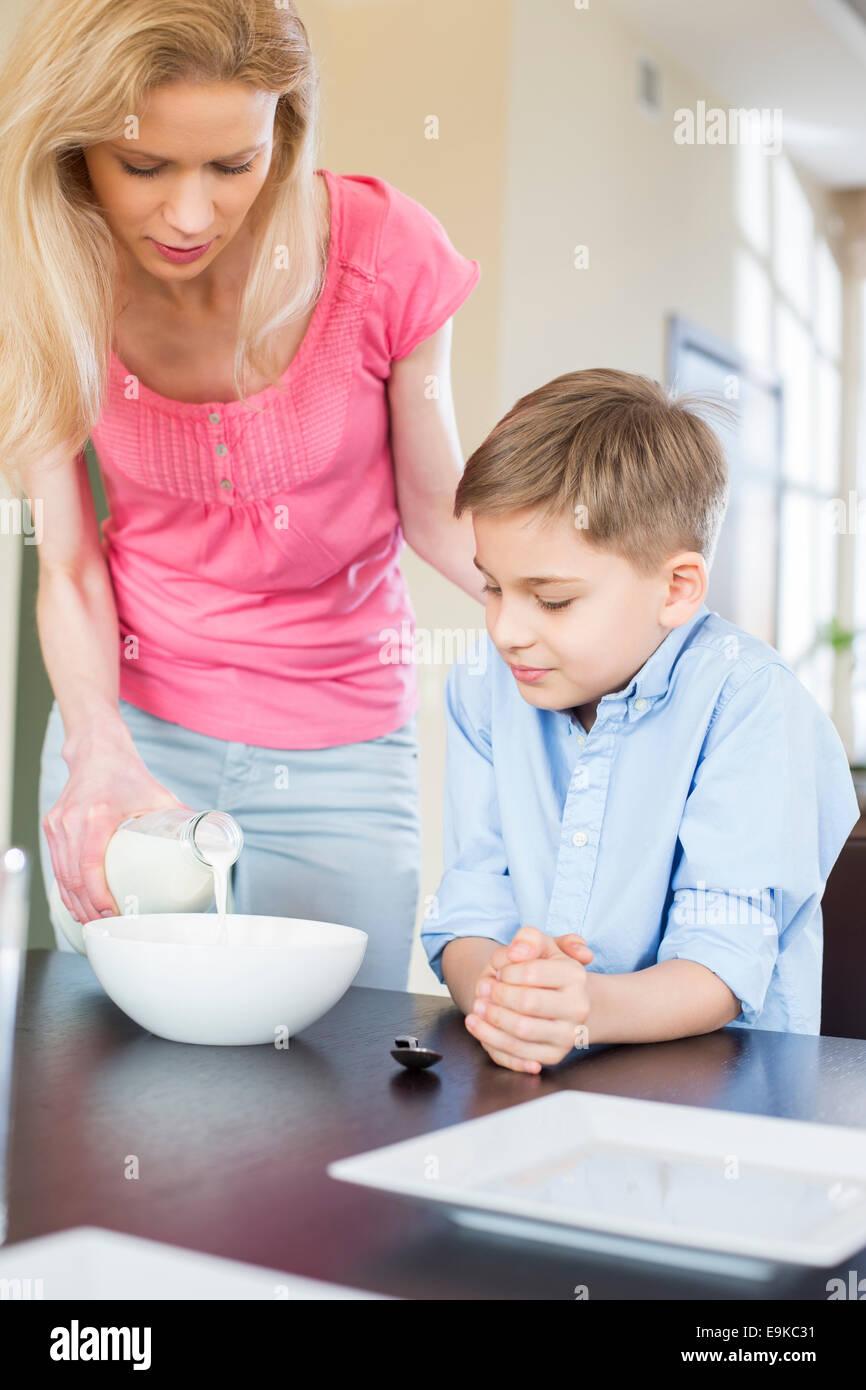 Verter la leche de la madre con el hijo en la mesa Imagen De Stock