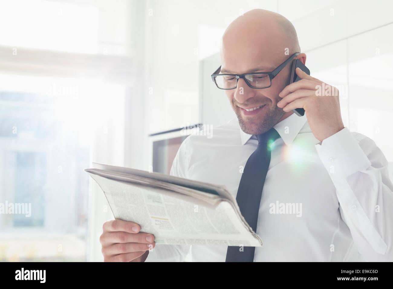 Feliz empresario llamada mientras la lectura de periódicos en casa Imagen De Stock