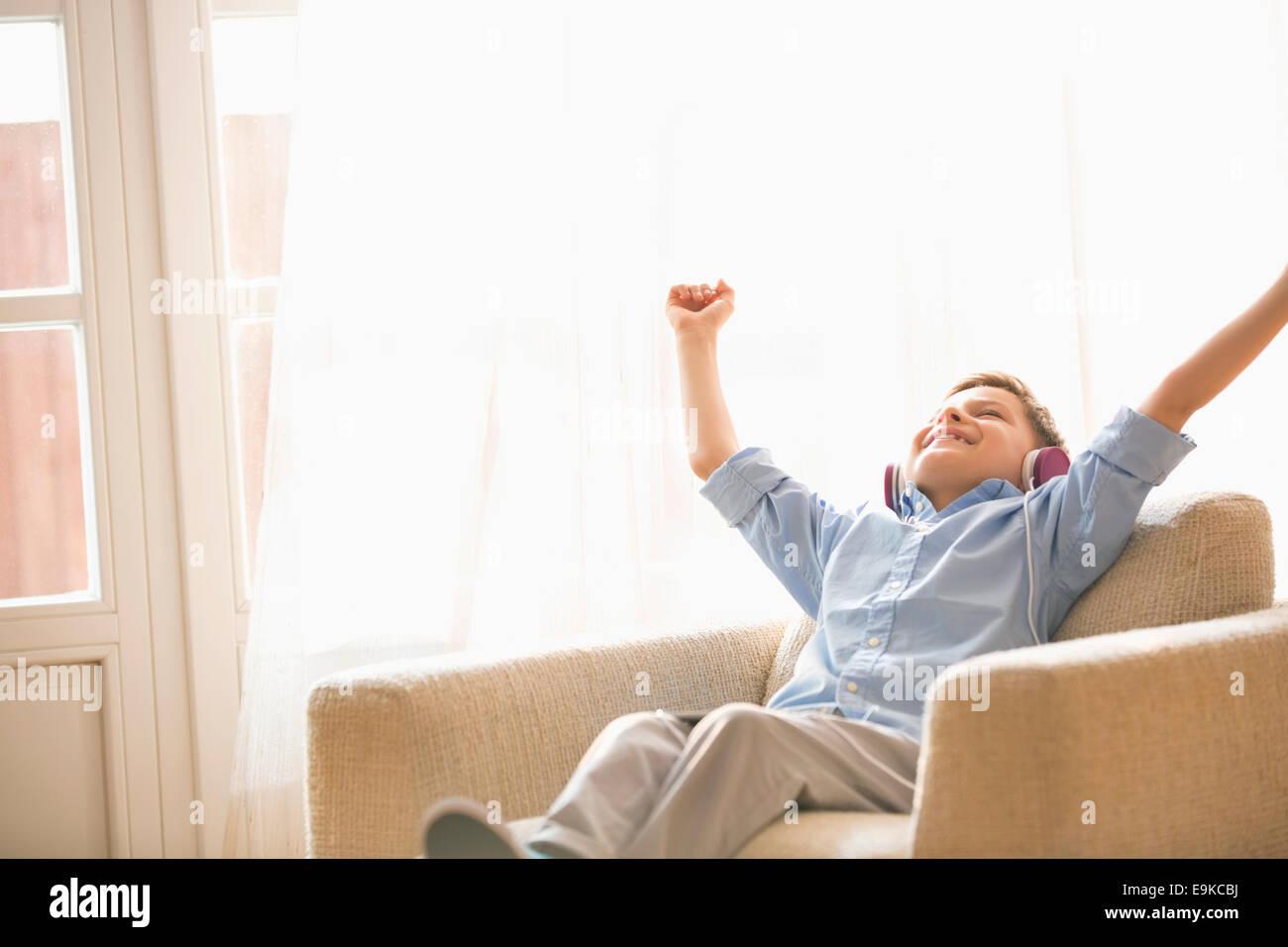 Muchacho feliz con los brazos levantados para disfrutar de la música mientras se relaja en un sillón en Imagen De Stock
