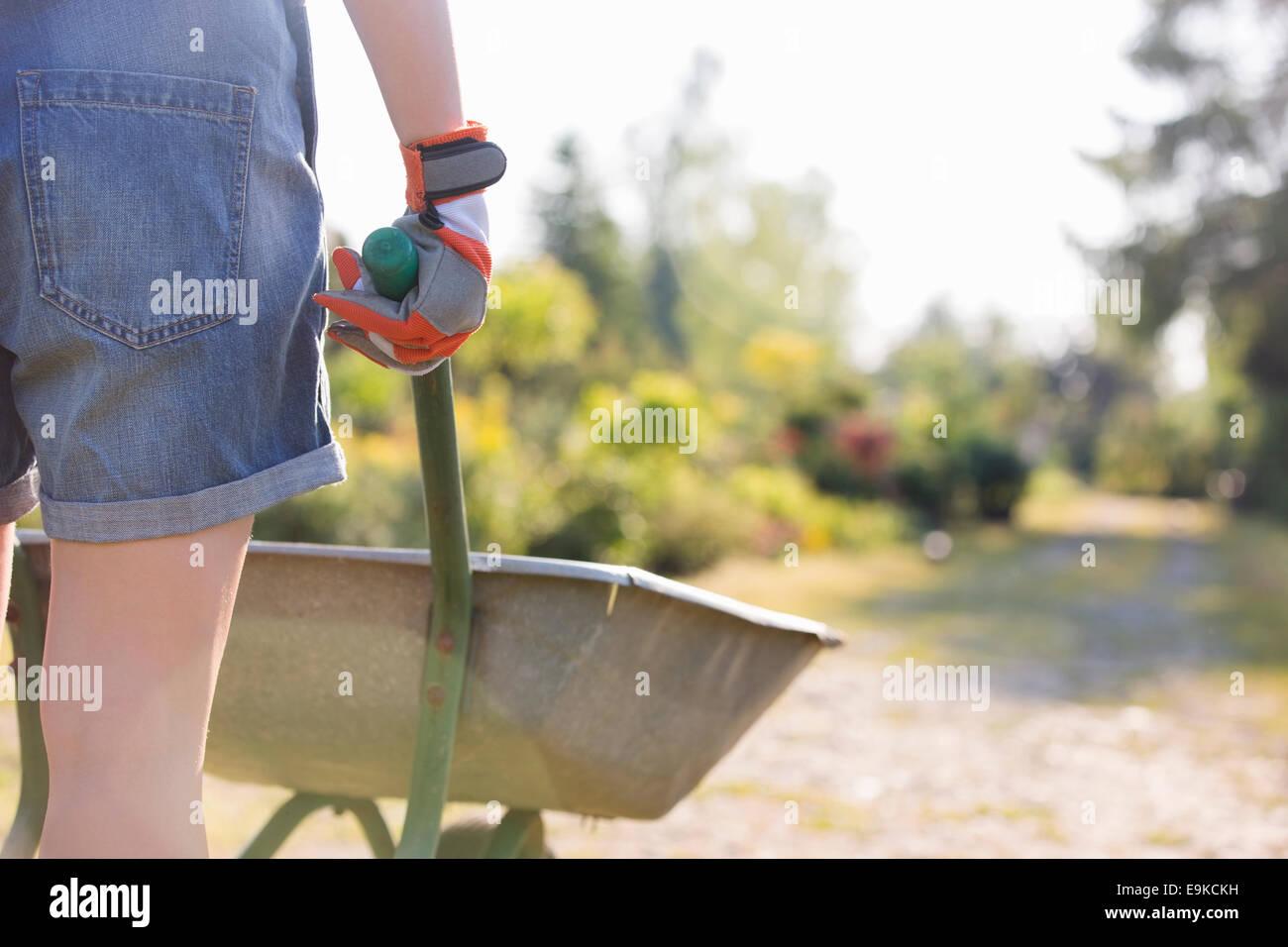 Vista posterior de la parte media del jardinero empujando la carretilla de mano femenina en el vivero de plantas Imagen De Stock