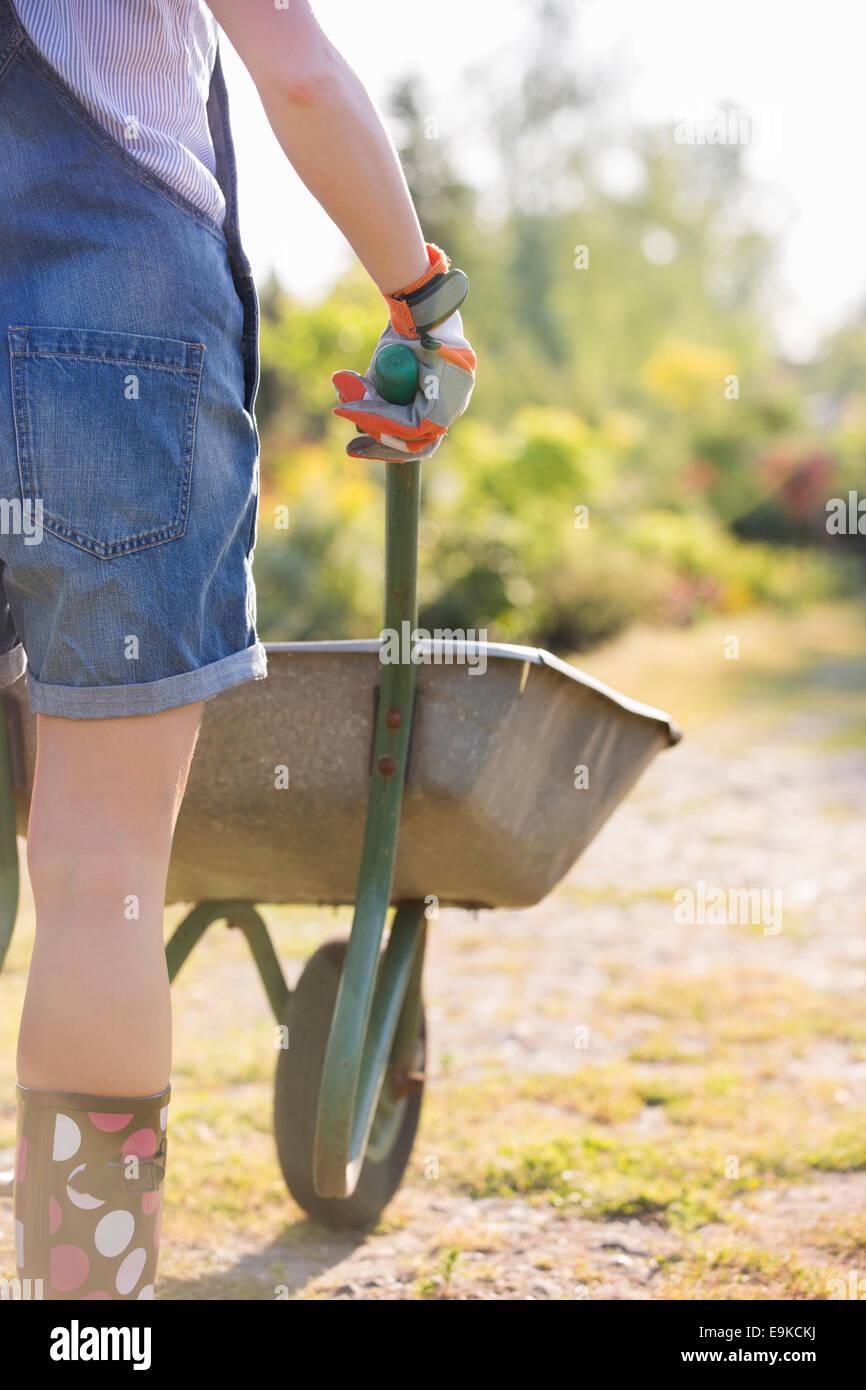 Vista posterior de la parte media del jardinero empujando la carretilla de mano femenina en el vivero de plantas Foto de stock