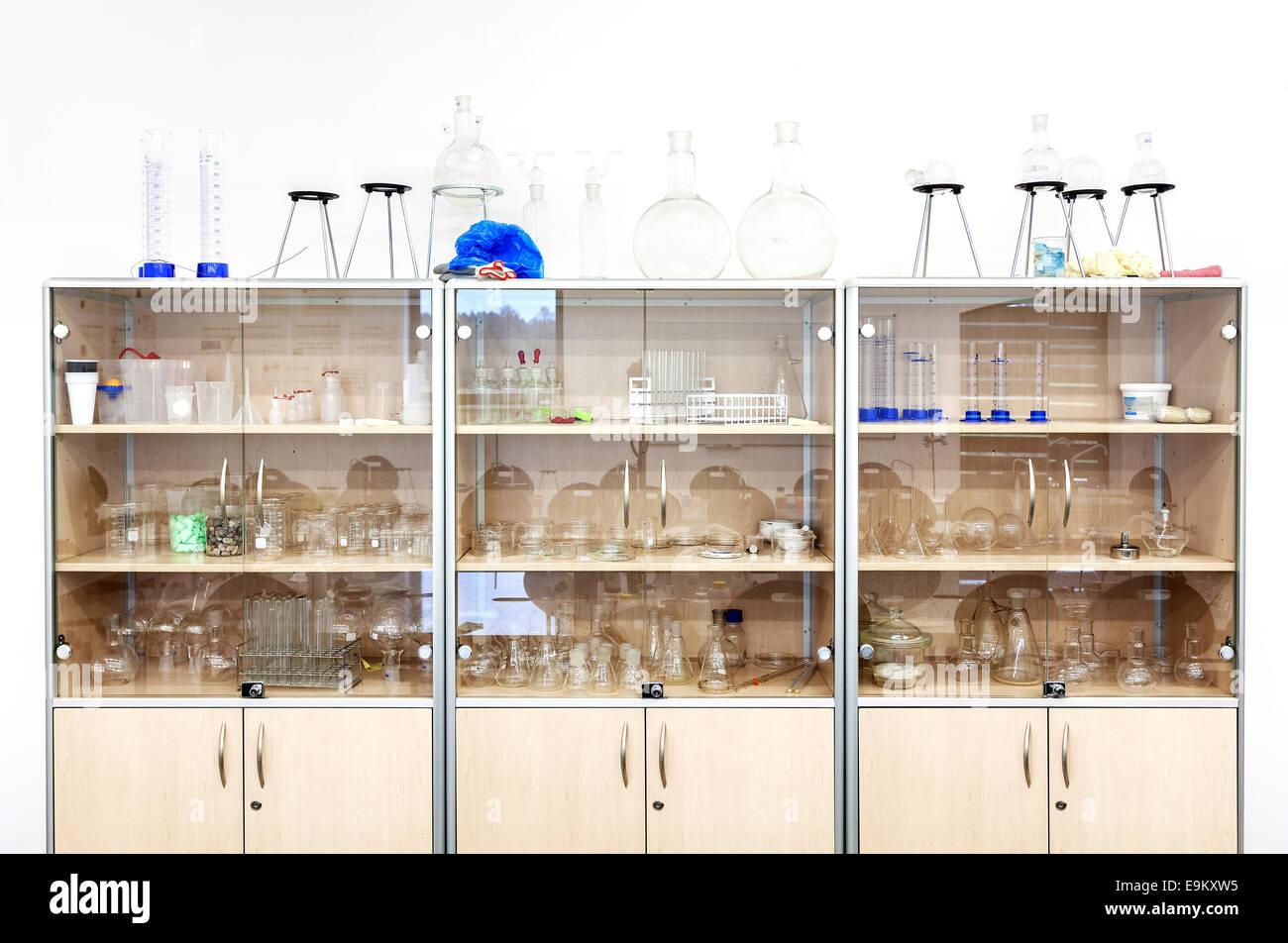 El material de vidrio de laboratorio y equipos diferentes en los estantes. Imagen De Stock