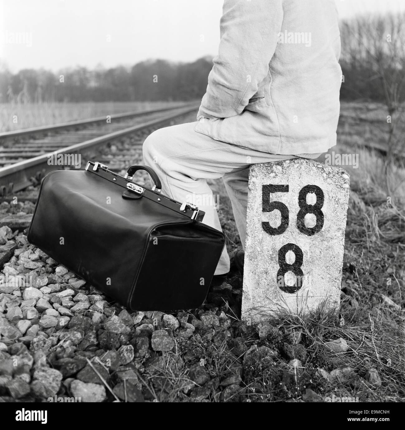 Una persona con una bolsa sentados junto a las vías del ferrocarril Imagen De Stock
