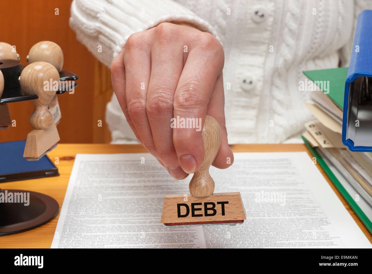Un sello con la inscripción deuda es sostenido en la mano Foto de stock